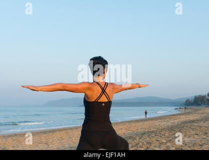 A woman practicing yoga warrior pose on a beach - Stock Image