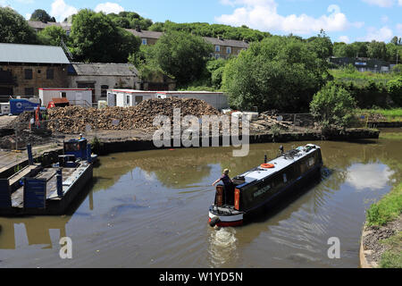 """Canal narrow boat """"Harlequin"""" makes a tight turn as it passes Finsley Gate wharf  on the Leeds and Liverpool canal in Burnley  19.6.19 - Stock Image"""