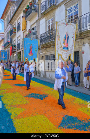Annual Corpus Christi Parade on streets covered in flower petal design.  Parade Participants. Ponte de Lima, Portugal, June 15, 2017 - Stock Image