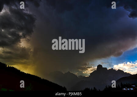 Storm clouds and downpour on the mountains of Alta Badia in summer sunset, Corvara in Badia - Trentino-Alto Adige, Italy - Stock Image