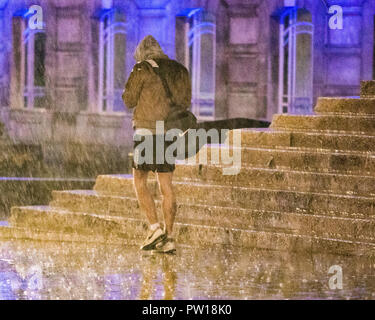 LEEDS, UK - 11 October 2018.  Short, but very sharp, rain showers caught people by surprise in Leeds this evening as dry conditions very quickly gave way to torrential rain showers. Man pictured in front of the Parkinson Building at Leeds University Credit: James Copeland/Alamy Live News - Stock Image