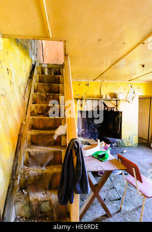 Stairs and furniture in an abandoned Irish cottage. - Stock Image