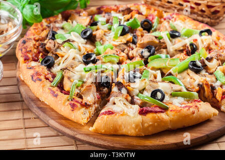 Spicy pizza with chicken gyros, green pepper, olives and onion on cutting board - Stock Image
