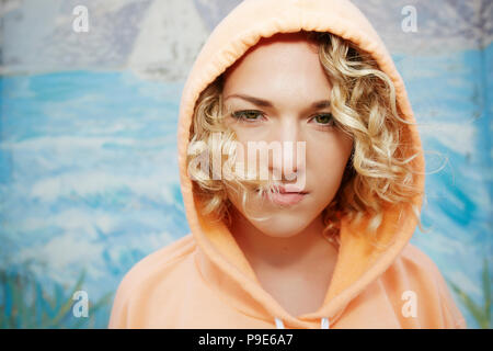 Portrait of woman with curly blond hair wearing pink hoodie, looking at camera. - Stock Image