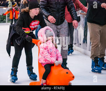 Edinburgh, Scotland, United Kingdom,  8th November 2018. Christmas celebrations: A busy Saturday in the capital city centre at Edinburghs Christmas celebration venue. Families enjoy the ice skating rink in St Andrew Square Gardens. A child being pushed on a seal ice aid - Stock Image