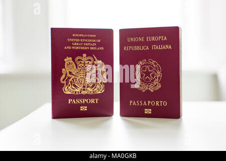 British and Italian passports standing next to each other. - Stock Image