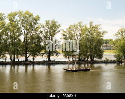 A traditional flat bottomed Loire riverboat passing the city of Orléans, Centre-Val de Loire, France, Europe - Stock Image