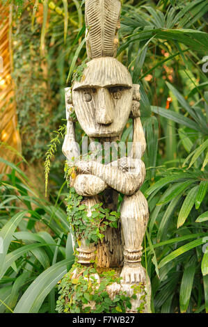 Southeast Asian overgrown tribal woodcarving in the jungle - Stock Image