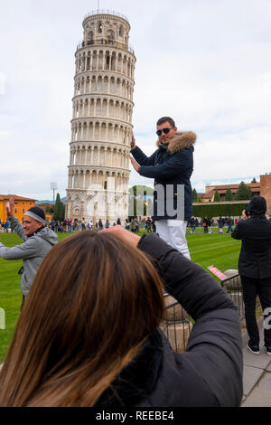 Italy Pisa Tuscany Leaning Tower tourists having fun with the lean - Stock Image