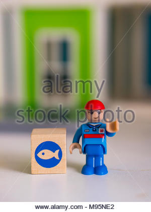 Poznan, Poland - March 17, 2018: Playtive toy service man standing next to a wooden box with fish symbol - Stock Image