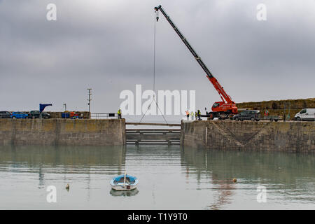 Mousehole, Cornwall, UK. 29th Mar, 2019. As the clocks go forward this weekend, heradling the start of British Summer Time, so the giant timber 'baulks' that protect Mousehole harbour during the winter months are lifted out, allowing the tiny fishing fleet, as well as leisure boats in and out of the harbour. Credit: Simon Maycock/Alamy Live News - Stock Image