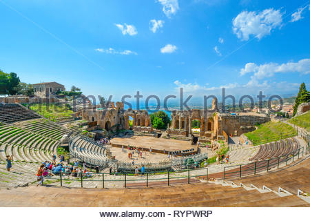 Tourists enjoy a summer afternoon at the ancient Greek Theatre on the Sicily at the resort city of Taormina, Italy. - Stock Image
