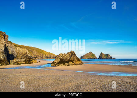 Rocks on Holywell Beach, with a view through  of the off shore Carters Rocks, Cornwall, UK - Stock Image