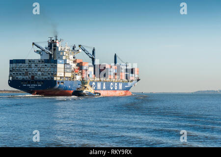 The Africa One container ship leaving the Port of Tilbury steaming downriver on the River Thames. - Stock Image