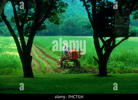 Farmer plowing his fields with old tractor in Pennsylvania countryside - Stock Image