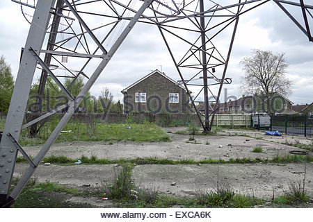 View of houses on housing estate, crossed by power lines, with base of electricity pylon in the foreground, Wednesbury, - Stock Image