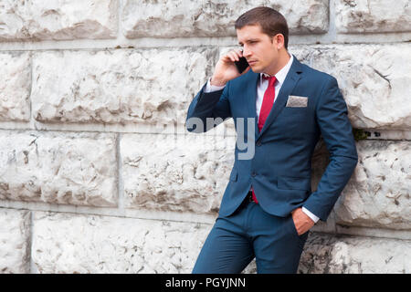 Young handsome businessman in a suit and tie talking at the smartphone agaist a marble wall - Stock Image