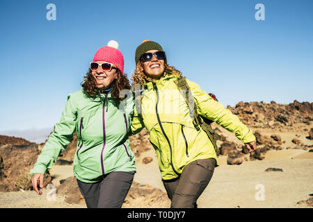 Happy cheerful couple of middle age women friends walking together at the mountain for alternative vacation - sunny day in outdoor leisure activity in - Stock Image