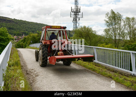 A farmer drives a tractor along an access road crossing the M56 motorway in Cheshire UK - Stock Image