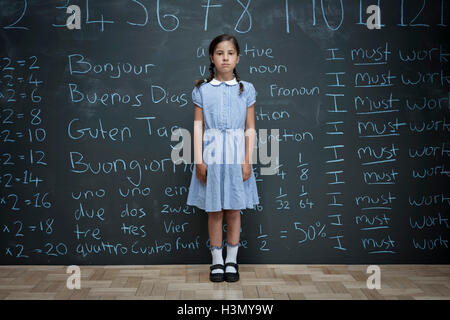 Portrait of schoolgirl standing in front of large chalkboard with schoolwork chalked on it - Stock Image