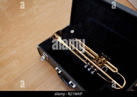 Gold trumpet in a black case on the floor, with copy space - Stock Image