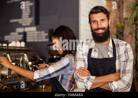 Portrait of waiter standing with arms crossed while waitress working in background - Stock Image