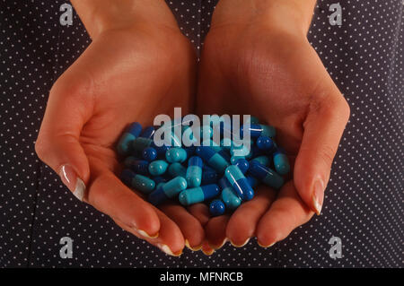 Pills in hand   Ref: CRB425_10046_105  Compulsory Credit: Synercomm/Photoshot - Stock Image