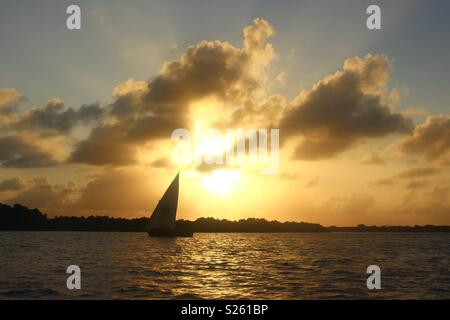 Dhow boat against the sunset in Lamu, Kenya - Stock Image