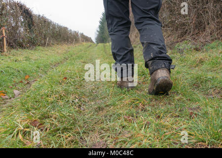 Legs of a woman walking in the  countryside clearly showing muddy hiking boots and dirty trousers - Stock Image