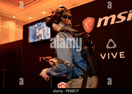 CES (Consumer Electronics Show) trade show attendee trying out game with wearable MSi computer-in-backpack with HTC Vive virtual reality VR  headset. - Stock Image