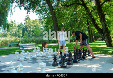 Father and son outdoors playing in large outdoor chess - Stock Image