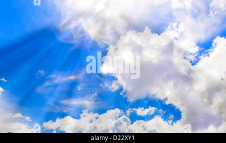 A dramatic cloudy sky, with gray clouds and the sun behind a cloud. - Stock Image