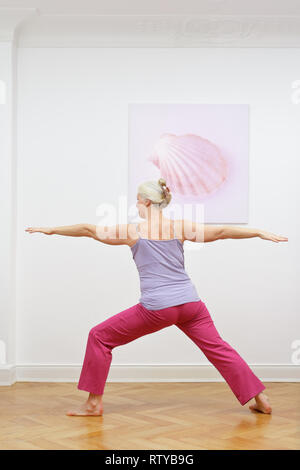 Senior woman with gray hair doing yoga exercises at home in front of a wall with a picture, asana warrior II - Stock Image