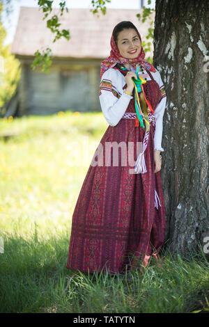 Young woman in traditional russian clothes standing under a tree and holding her pigtail - vertical shot - Stock Image