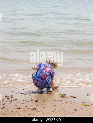 A small boy on a beach in summer bending down to play with the sea water - Stock Image