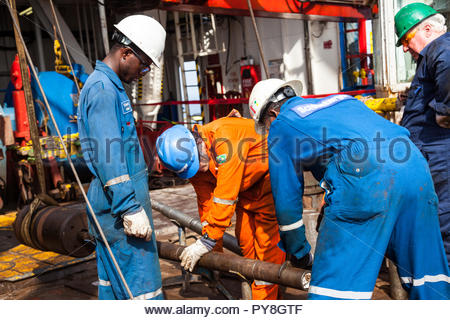 Workers holding machinery on offshore oil platform - Stock Image