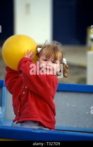 little girl standing in boat on the beach holding a big yellow balloon - Stock Image
