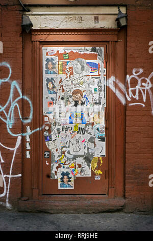 A street art collage of stickers, drawing, graffiti and tagging on a door on Eighth Avenue near 14th Street in Chelsea, Manhattan, New York City - Stock Image