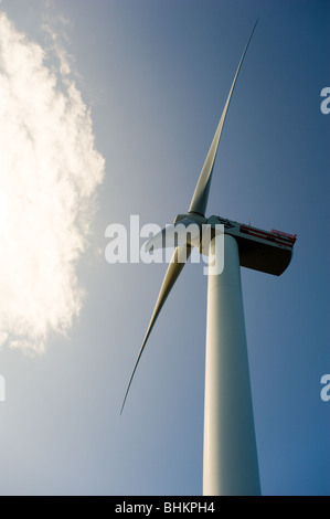image of looking up at offshore wind turbine with sun behind cloud - Stock Image