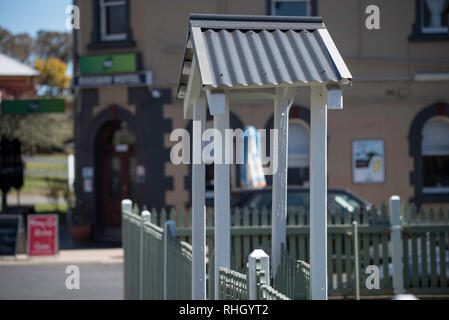 A small timber and tin roofed, arched gate sits neatly between a line of painted picket fence surrounding a home in Millthorpe, New South Wales, Aust. - Stock Image