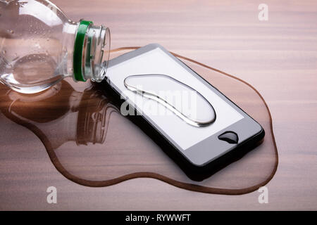 Close-up Of Spilled Water On Smart Phone Over Wooden Desk - Stock Image