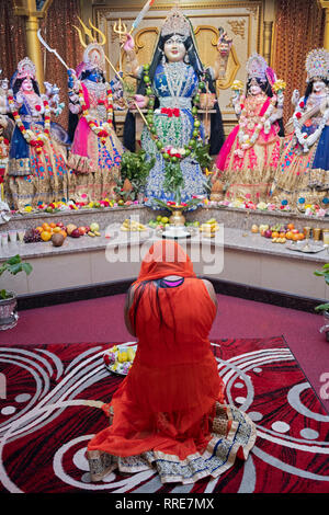 An anonymous Hindu woman kneels in prayer and meditation in front of statues of deities in Queens, New York City - Stock Image