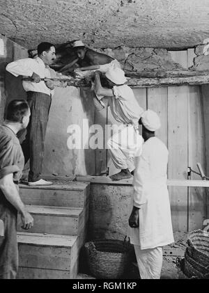 Howard Carter who discovered Tutankhamun's Tomb in the Valley of the Kings, Luxor, Egypt. November 1922. Carter using a pry bar inside the tomb. Scanned from image material in the archives of Press Portrait Service (formerly Press Portrait Bureau) - Stock Image