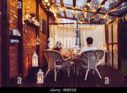 Young couple man and woman sit on white rattan garden chairs on wooden romantic outdoor terrace in the evening celebrating and toasting, spending time - Stock Image