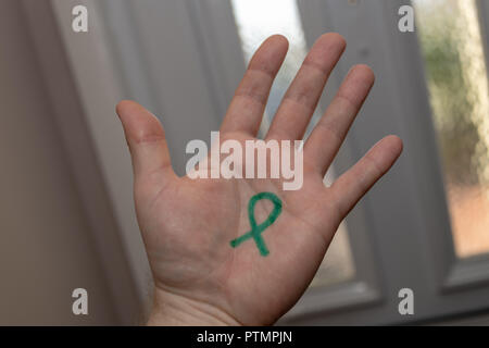 Poole, UK. 10th October 2018. A green ribbon drawn on a hand in support of World Mental Health Day. Green ribbons are used to raise awareness and support good mental health. The day provides an opportunity for all working on mental health issues to talk about their work, and what more needs to be done to make mental health care a reality for people worldwide. Credit: Thomas Faull/Alamy Live News - Stock Image