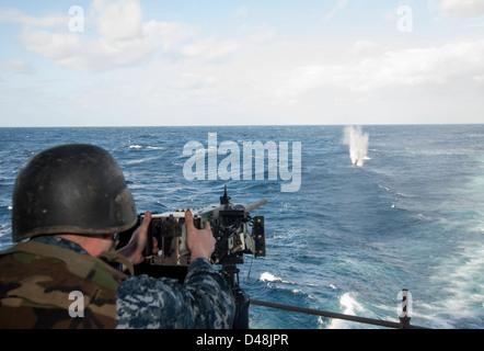 A Sailor fires a machine gun at sea. - Stock Image