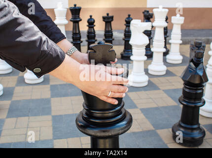 man moving giant chess piece king outdoor on the city street. hands closeup - Stock Image