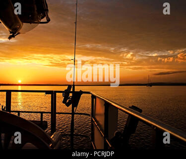 The Firmament housing a brilliant atmospheric cloudy Golden Yellow and Grey sky sunset display from a boat over water and through prominant Stratus cl - Stock Image