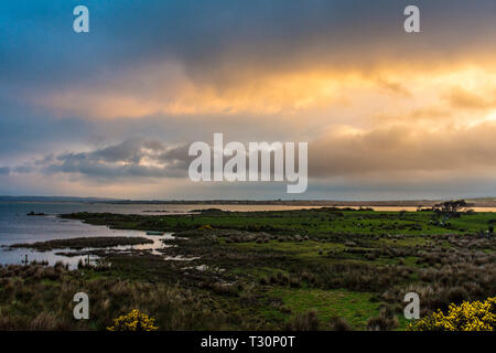Ardara, County Donegal, Ireland. 5th April 2019. The rising sun illuminates clouds on a cold morning on the north-west coast. Credit: Richard Wayman/Alamy Live News - Stock Image