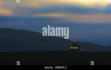 Small lighted hut against dark hill at twilight. - Stock Image